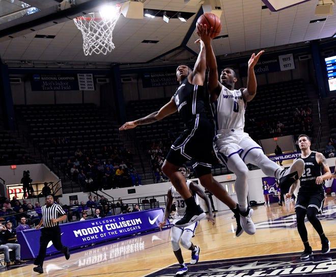 Abilene Christian's Jaylen Franklin floats the ball past Khaleem Bennett during Saturday's men's basketball game against Central Arkansas Jan. 26, 2019. Final score was 79-56, ACU.