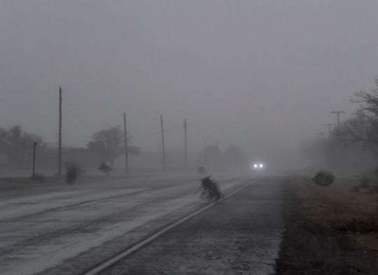 Tumbleweeds are blown across State Highway 6 south of Rule as a thunderstorm blows in from the west Dec. 26.