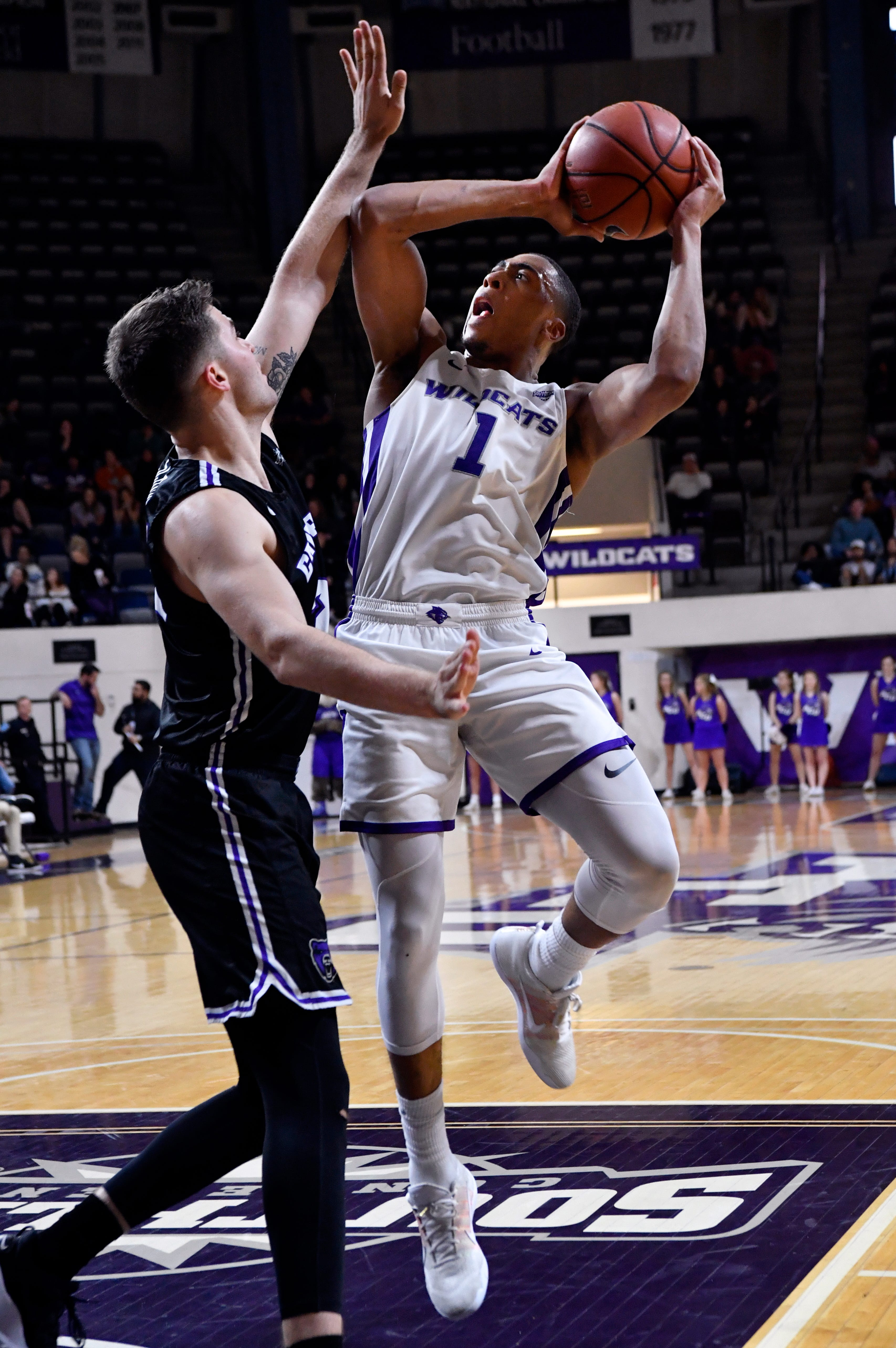 Abilene Christian's Jaren Lewis attempts to shoot over Tanner Schmit during Saturday's men's basketball game against Central Arkansas Saturday Jan. 26, 2019. Final score was 79-56, ACU.
