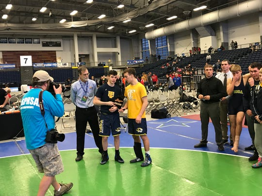 Tioga seniors John Worthing, middle, and Austin Lamb, right, hold the state semifinal plaque as Section 4 wrestling coordinator Rick Armstrong looks on during Saturday's NYSPHSAA Dual Meet Tournament at SRC Arena.