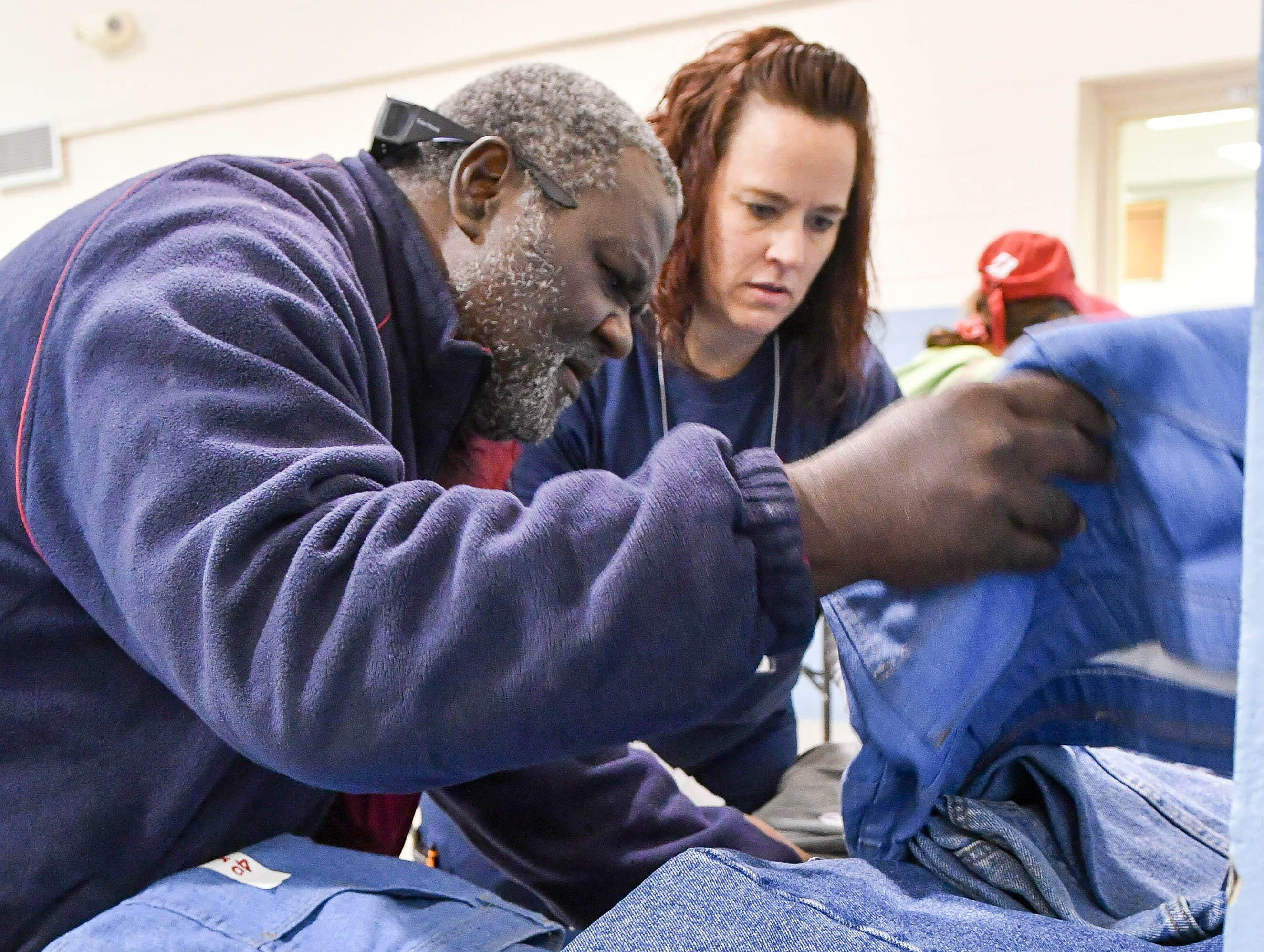 Heather Skinner helps Kenneth Harvey find a pair of jeans in this size during Saturday's Stand Down for Veterans at Cocoa Armory.