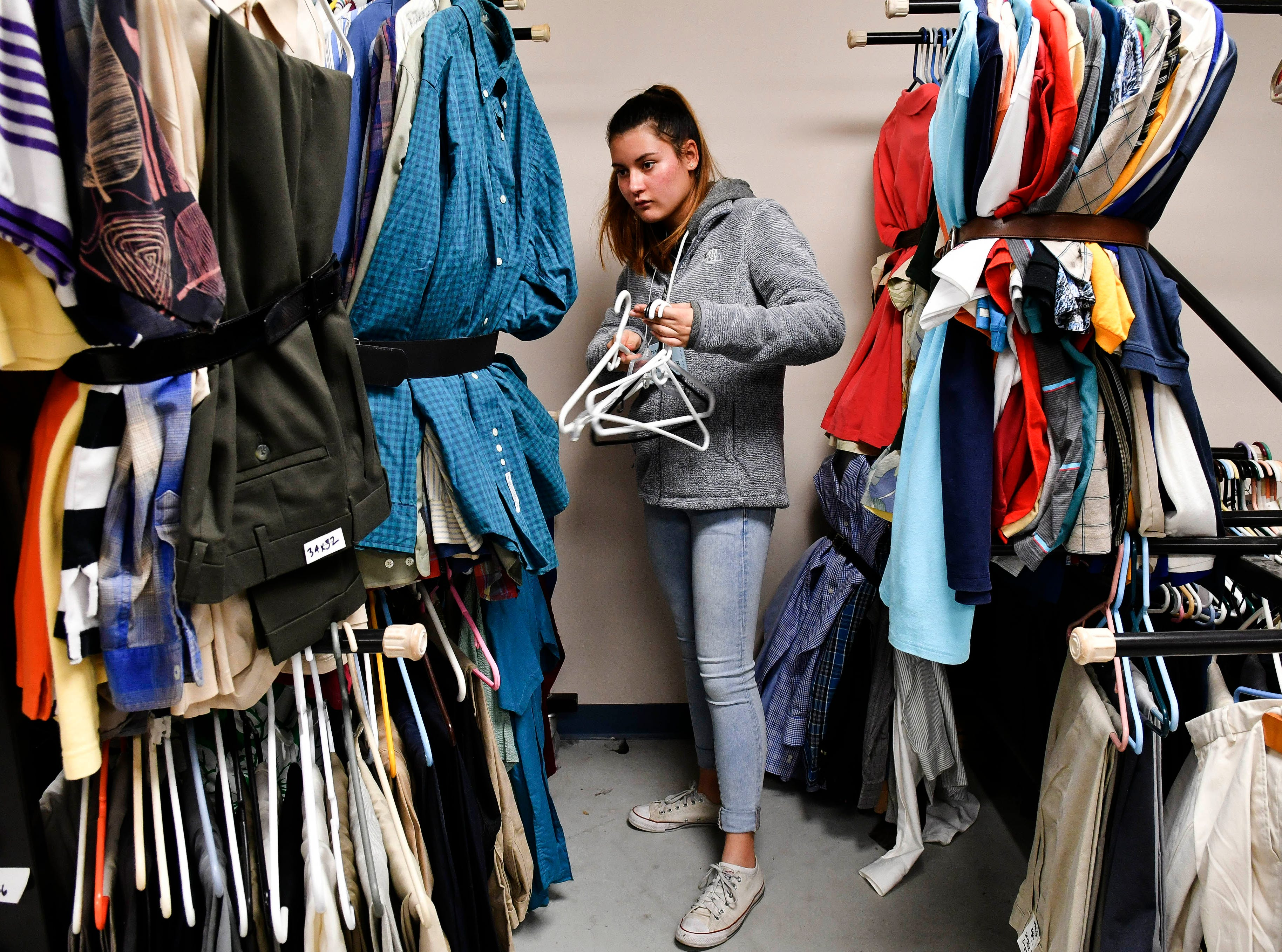 Viera High volunteer Sayako Vanoss helps collect empty hangars during Saturday's Stand Down for Veterans at Cocoa Armory. 167 veterans were given assistance today ranging from food, shoes and other clothing items to free haircuts and medical care.