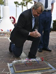 Mike Leinbach, former Shuttle Launch Director at Kennedy Space Center, lays a flower of the plaque of astronaut Michael P. Anderson during the Astronaut Memorial Ceremony at Sand Point Park in Titusville. Anderson was killed when space shuttle Columbia disintegrated upon reentry into Earth's atmosphere.