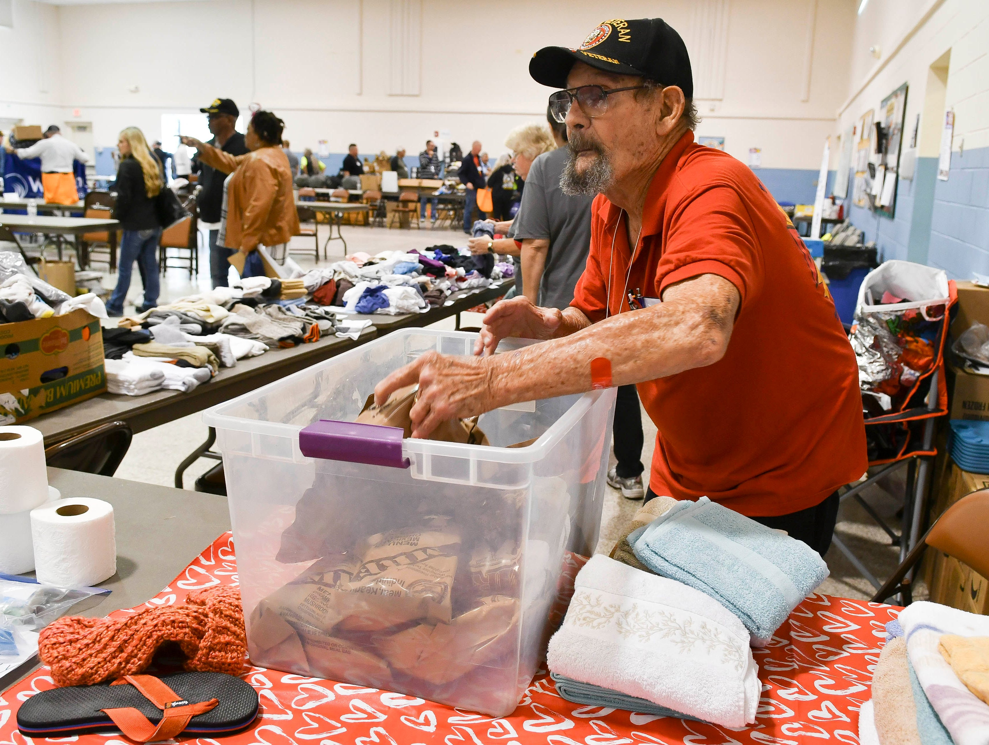 Tom Northcutt, a volunteer with the VFW Post 4228 Auxiliary helps distribute MRE's during Saturday's Stand Down for Veterans at Cocoa Armory.