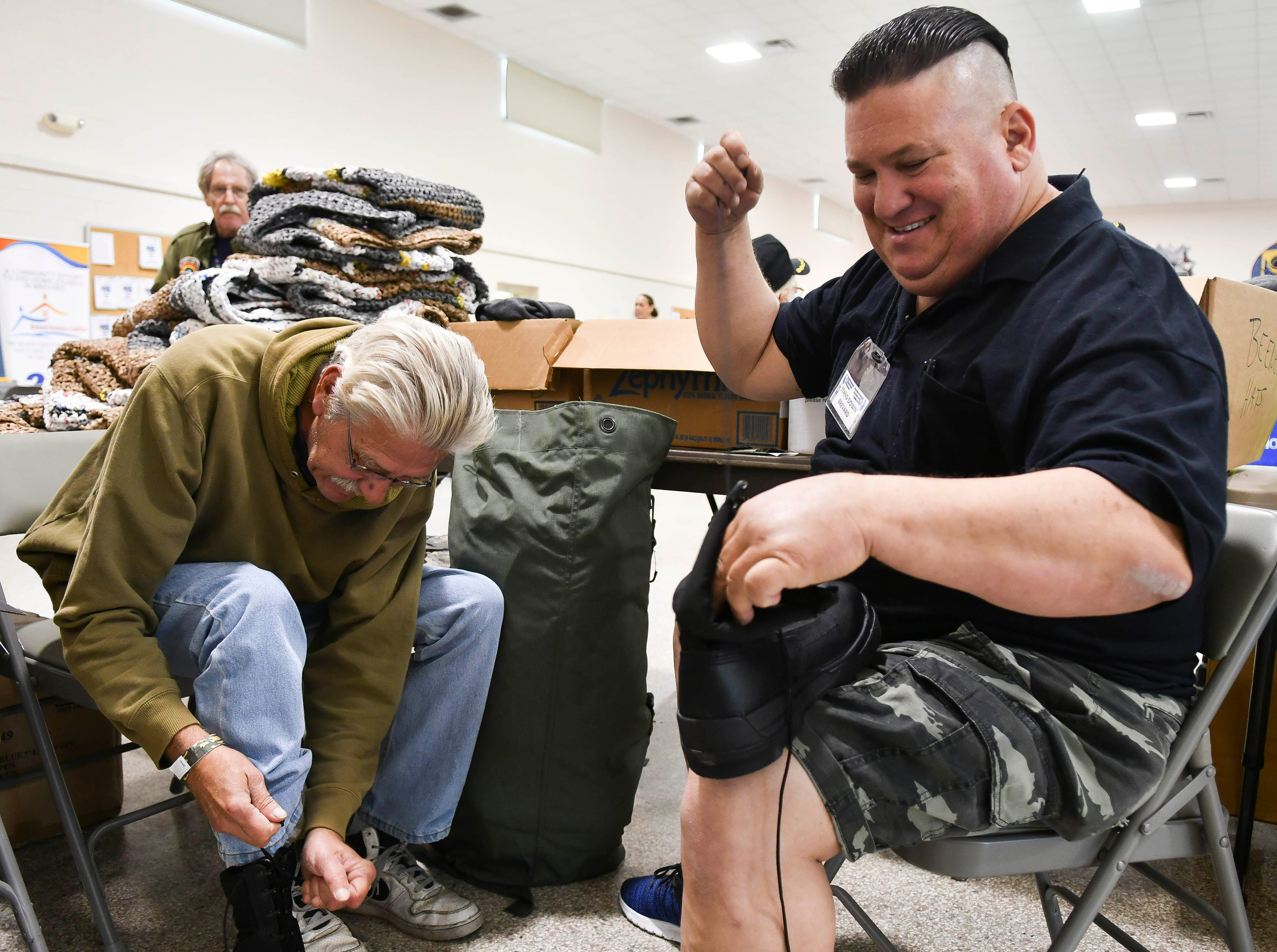 Ronnie Sathre II laces a pair of boots for Ray Bartels to try on during Saturday's Stand Down for Veterans at Cocoa Armory.
