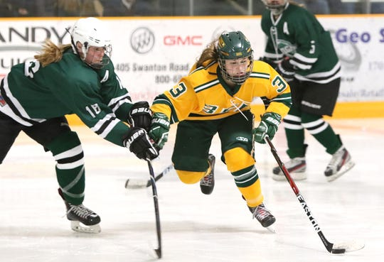 BFA-St. Albans' McKenna Remillard tries to elude a stick check by Rice Memorial's Michelle Essien in the Comets' 2-0 win over the Green Knights on Saturday night, Jan. 26 at the Collins-Perley Sports Complex in St. Albans.