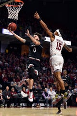 Cincinnati Bearcats guard Logan Johnson (0) shoots the ball past Temple Owls guard Nate Pierre-Louis (15) during the first half at Liacouras Center.