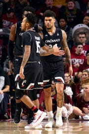 Cincinnati Bearcats guard Jarron Cumberland (34) celebrates with guard Cane Broome (15) and forward Eliel Nsoseme (22) after scoring during the second half against the Temple Owls at Liacouras Center.