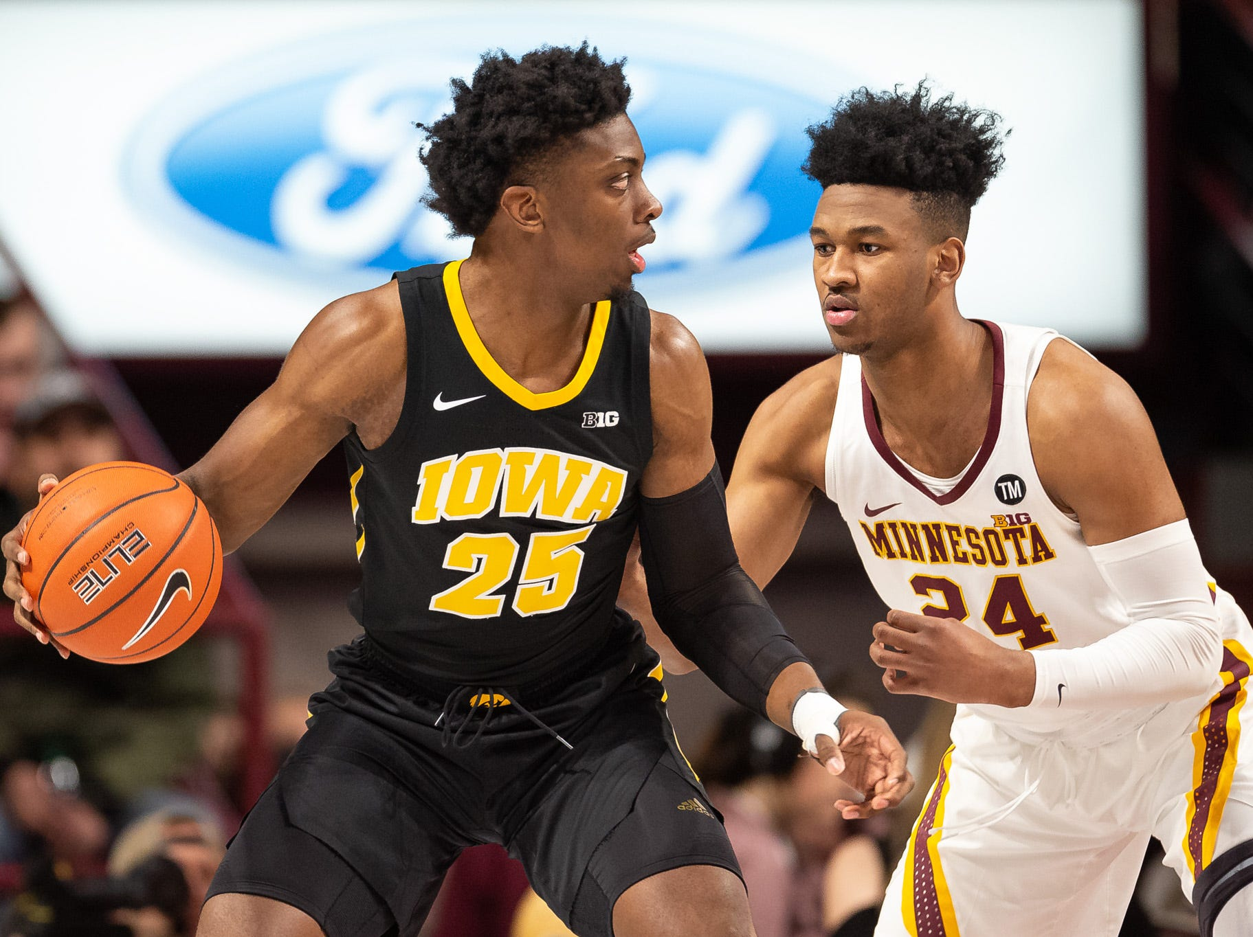 Iowa Hawkeyes forward Tyler Cook (25) dribbles the ball as Minnesota Gophers forward Eric Curry (24) defends during the first half at Williams Arena.