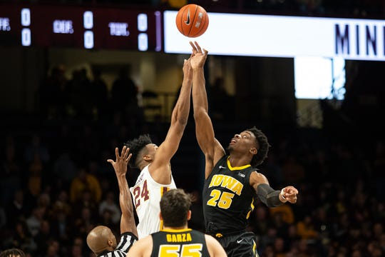 Iowa Hawkeyes forward Tyler Cook (25) and Minnesota Gophers forward Eric Curry (24) battle for the ball during the first half at Williams Arena.