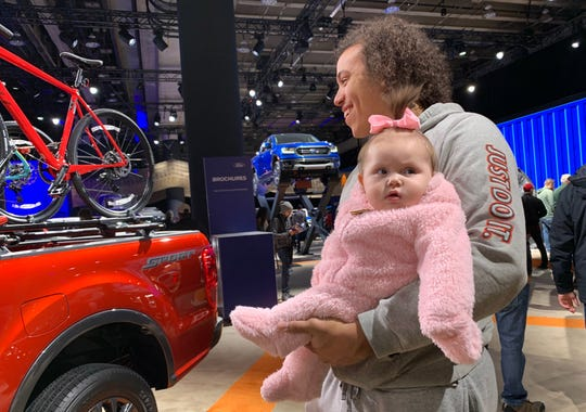 Marcus Jamison of Marine City with his 7-month-old daughter Arielle Jamison, during Arielle's first trip to the North American International Auto Show at Cobo Center on Jan. 27, 2019.