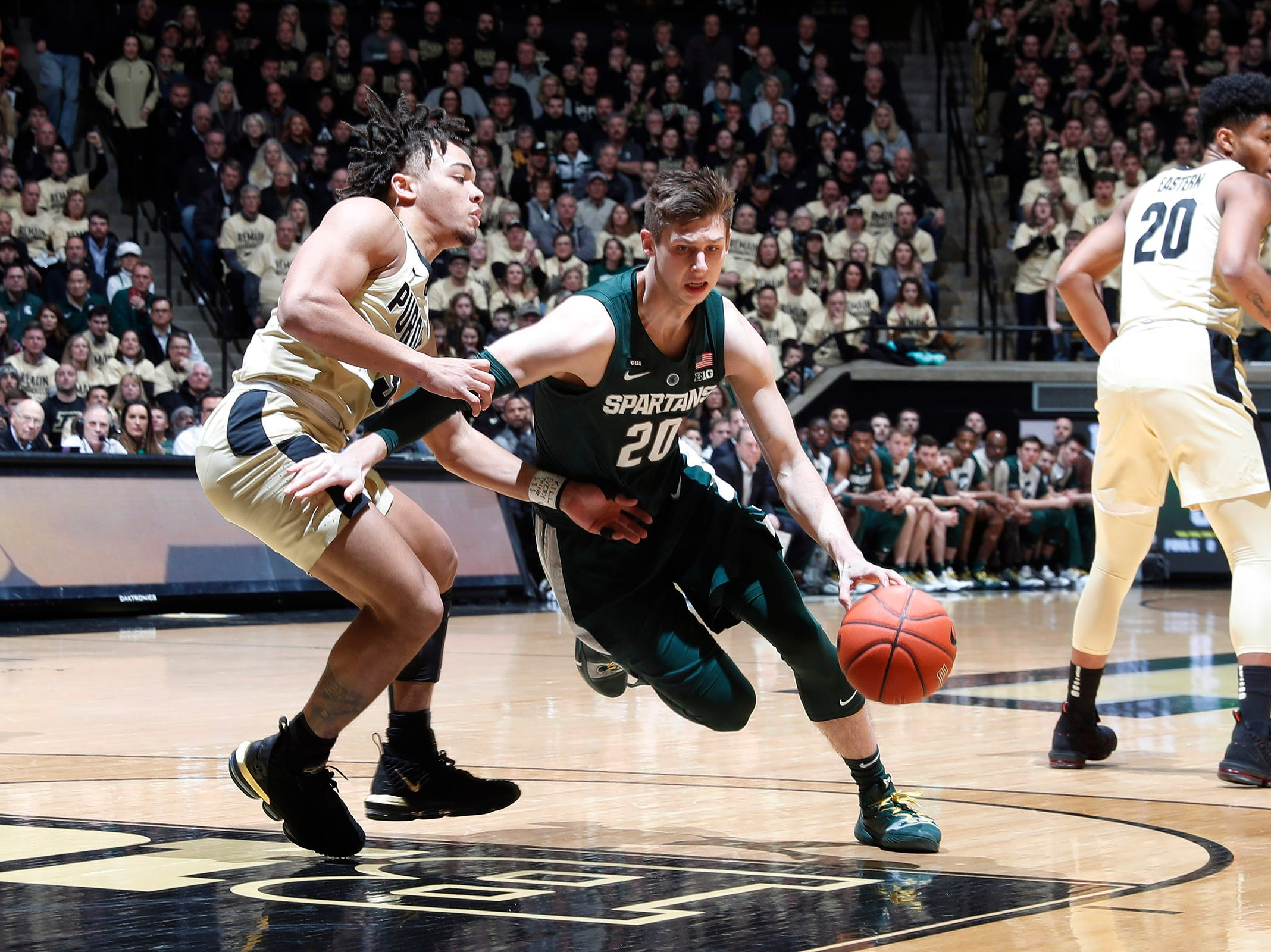 Michigan State guard Matt McQuaid dribbles the ball around Purdue guard Carsen Edwards during the first half on Sunday, Jan. 27, 2019, in West Lafayette, Ind.