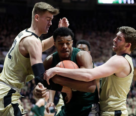 Xavier Tillman is tied up by Purdue's Matt Haarms, left, and Ryan Cline during the first half Sunday in West Lafayette, Ind.