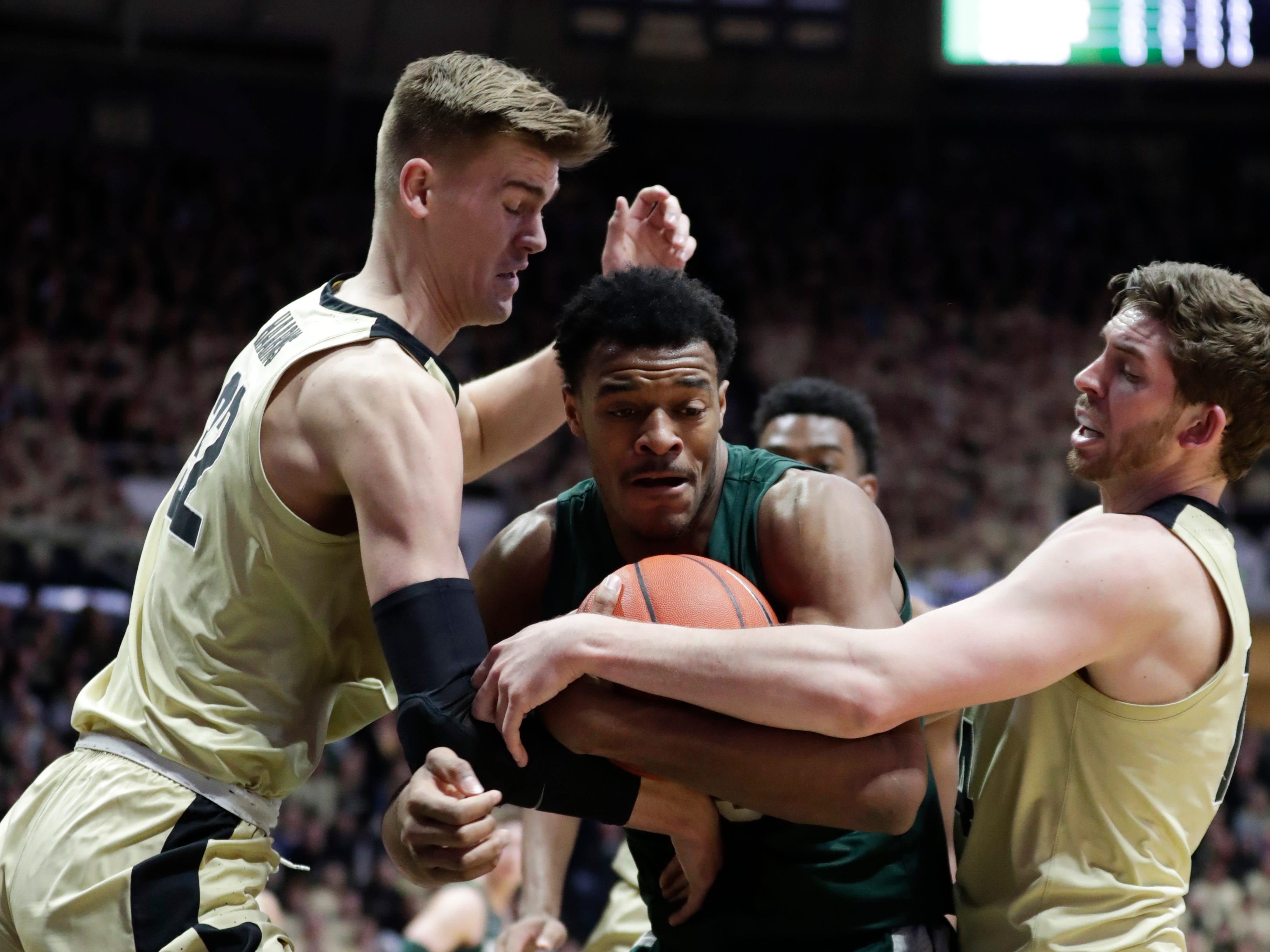 Michigan State forward Xavier Tillman is tied up by Purdue center Matt Haarms, left, and guard Ryan Cline during the first half on Sunday, Jan. 27, 2019, in West Lafayette, Ind.