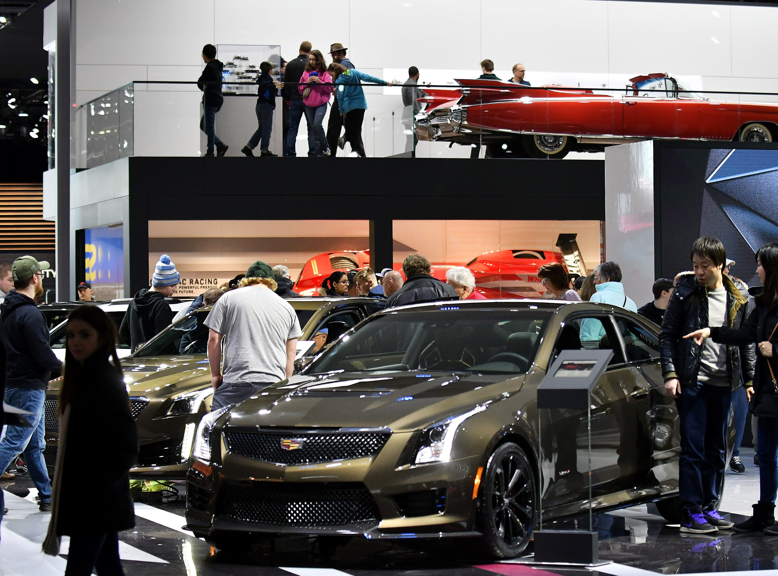 People check out the cars at the Cadillac display including the ATS.