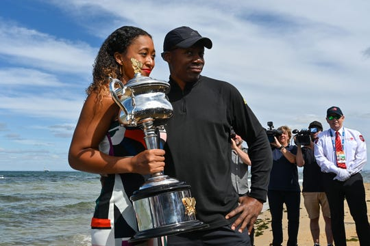 Japan's Naomi Osaka and her father Leonard Francois pose for photographs with the championship trophy Sunday at the Brighton Beach in Melbourne.