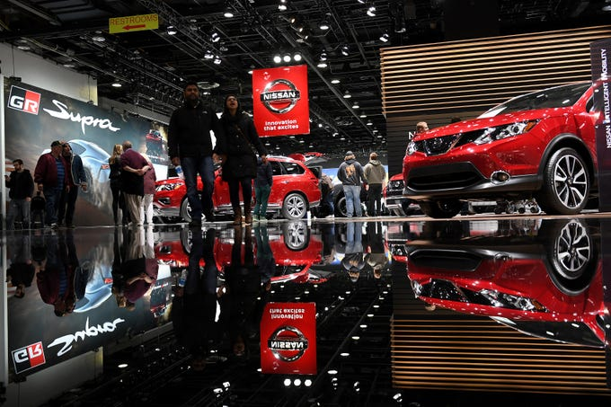 People walk through the Nissan display during the final day of the North American International Auto Show at Cobo Center, in Detroit on Jan. 27, 2019.