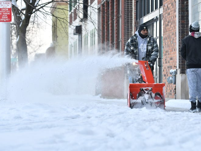 Fernando Parraz clears snow from a sidewalk in Detroit on Sunday.  On Monday, Five to seven inches of snow are expected in Oakland and Macomb counties, while three to five inches are expected in Wayne and Washtenaw.