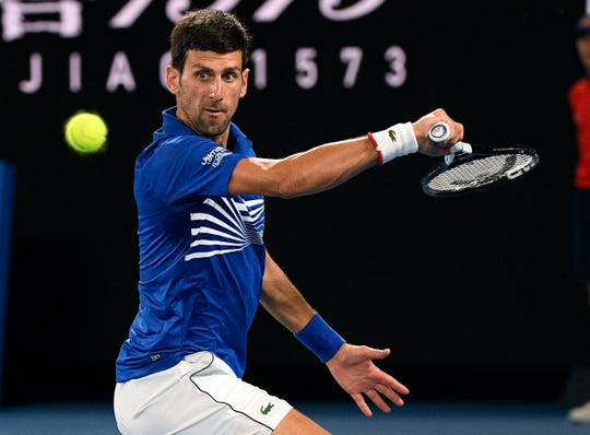 Novak Djokovic makes a backhand return to Rafael Nadal during the men's singles final at the Australian Open.