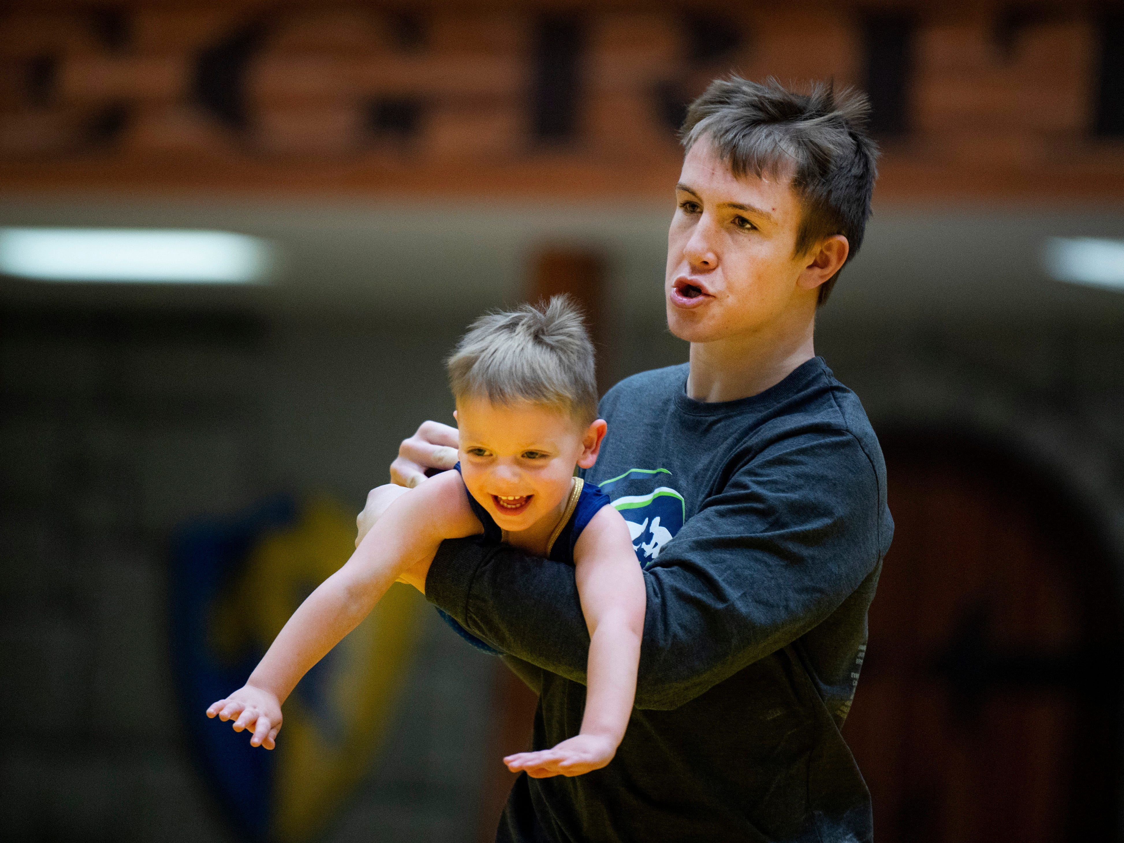 Ian Hartz takes Axel Deters, 2, for a flight around the wrestling mats at the IHSAA Sectional at Castle High School Saturday afternoon. Axel is the grandson of coach Bob Harmon and his dad, Matt Deters, was Harmon's first state champion wrestler at Castle.