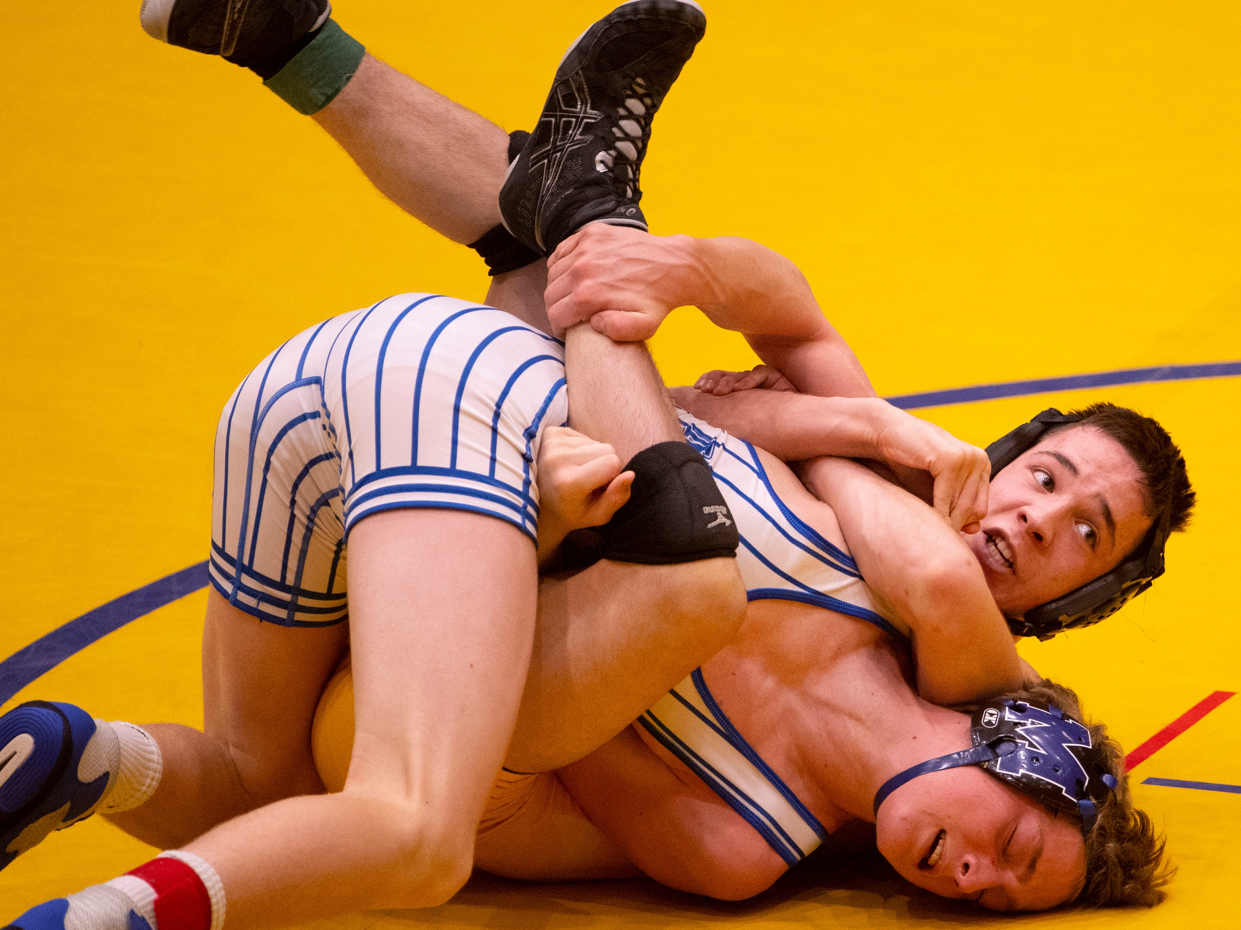 Castle's Sean Moore, top, holds onto Memorial's Aiden Farmer during their 138-pound championship match at the IHSAA Sectional at Castle High School Saturday afternoon. Moore beat Farmer 8-4.