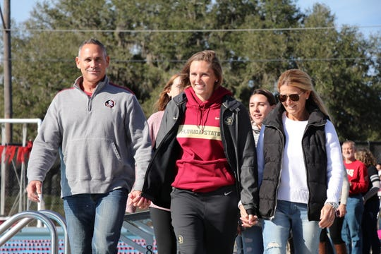 Senior swimmer McKenna Keith and her parents, Michael (left) and Ginger (right), attended their daughter's final FSU swim meet.