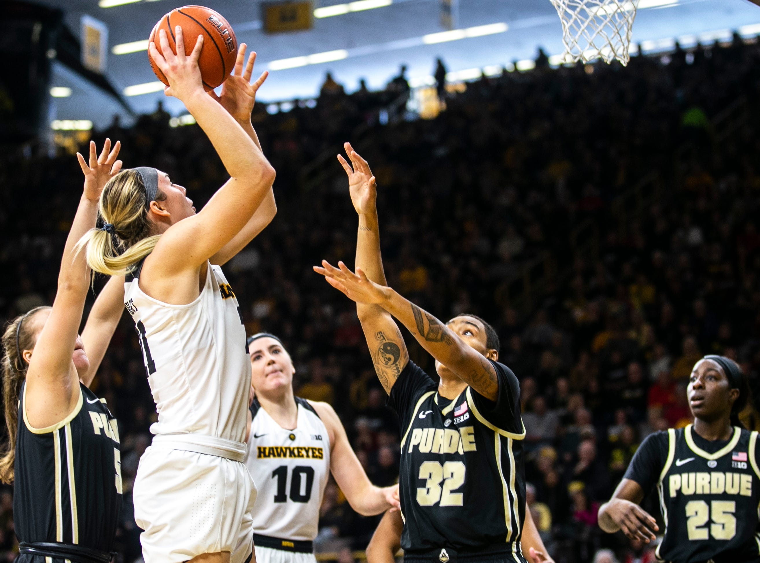 Iowa forward Hannah Stewart (21) drives to the basket past Purdue's Cassidy Hardin (5) and Ae'Rianna Harris (32) during a NCAA Big Ten Conference women's basketball game on Sunday, Jan. 27, 2019, at Carver-Hawkeye Arena in Iowa City, Iowa.