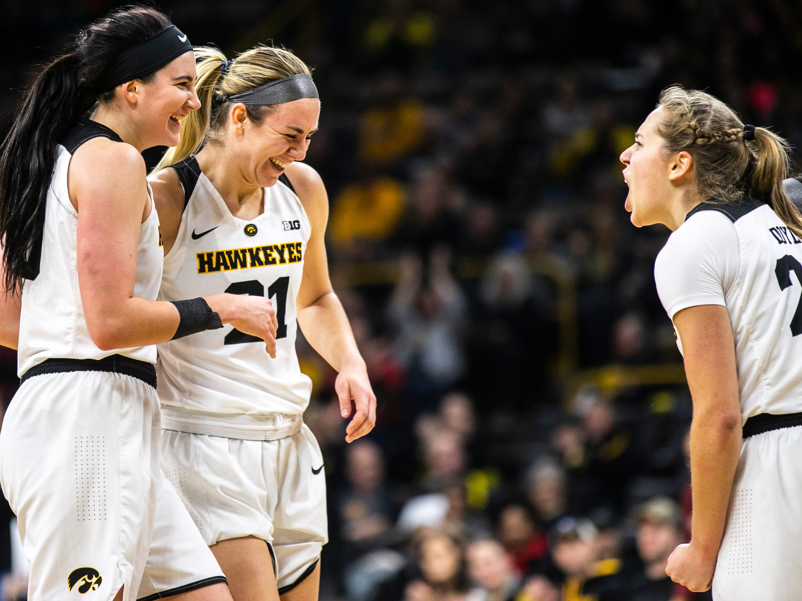 Iowa forward Hannah Stewart (21) is embraced by Megan Gustafson, left, while Kathleen Doyle, right, celebrates during a NCAA Big Ten Conference women's basketball game on Sunday, Jan. 27, 2019, at Carver-Hawkeye Arena in Iowa City, Iowa.