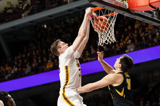 Minnesota center Matz Stockman dunks over Iowa's Ryan Kriener on Sunday at Williams Arena. The Gophers ravaged the Hawkeyes in the first half and hung on to win 92-87.