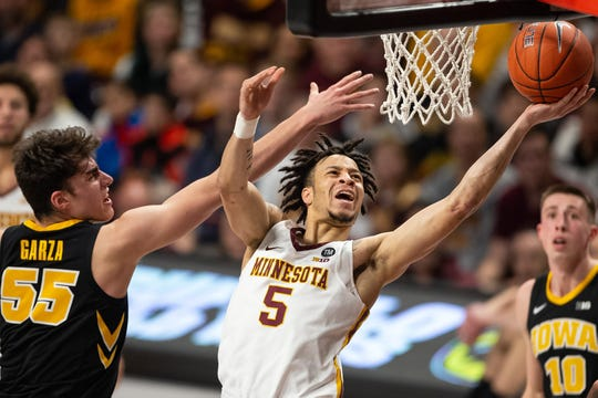 Jan 27, 2019; Minneapolis, MN, USA; Minnesota Gophers guard Amir Coffey (5) shoots the ball as Iowa Hawkeyes forward Luka Garza (55) defends during the first half at Williams Arena. Mandatory Credit: Harrison Barden-USA TODAY Sports