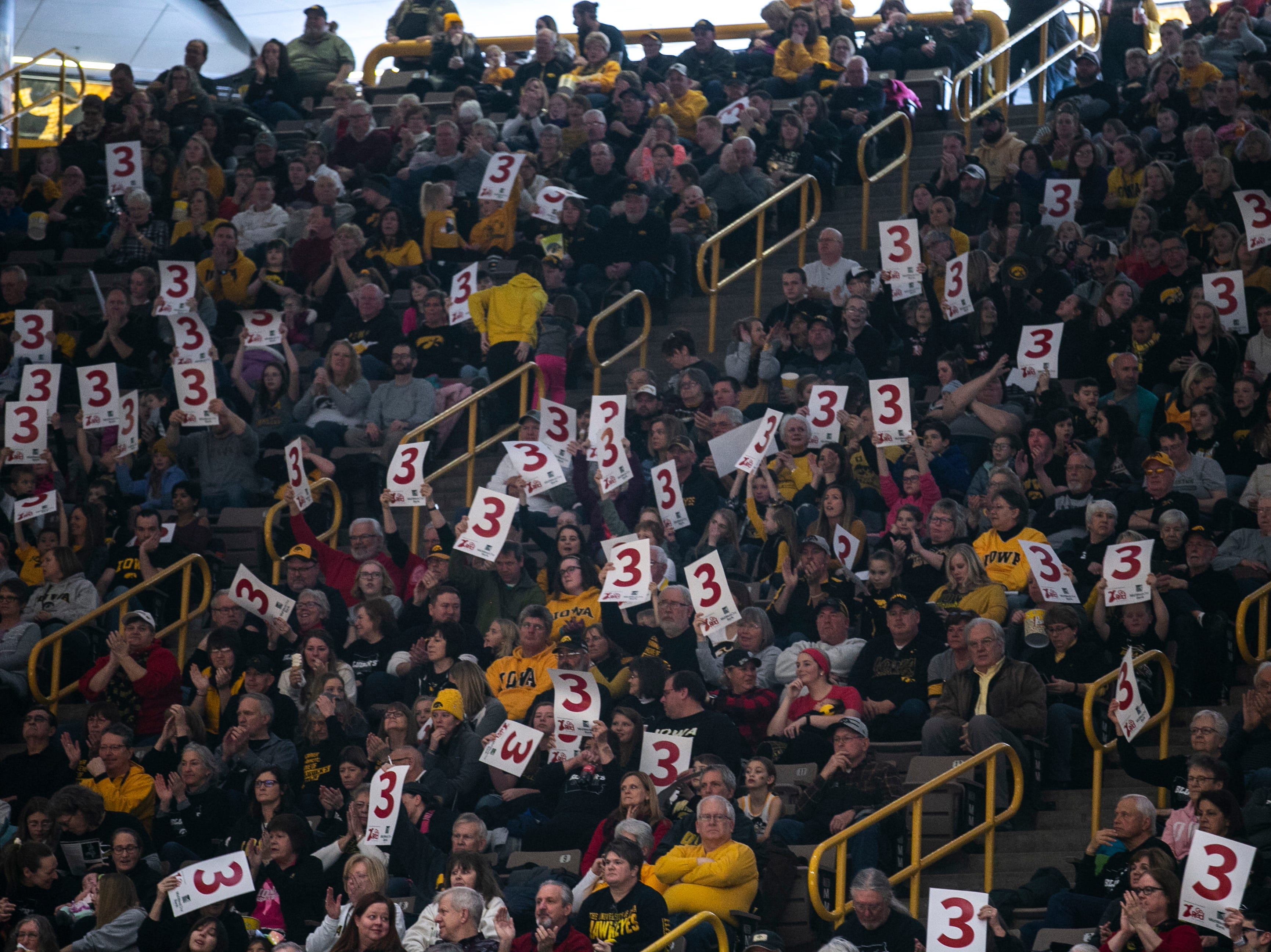 "Iowa Hawkeyes fans hold up ""3"" signs after deep basket during a NCAA Big Ten Conference women's basketball game on Sunday, Jan. 27, 2019, at Carver-Hawkeye Arena in Iowa City, Iowa."