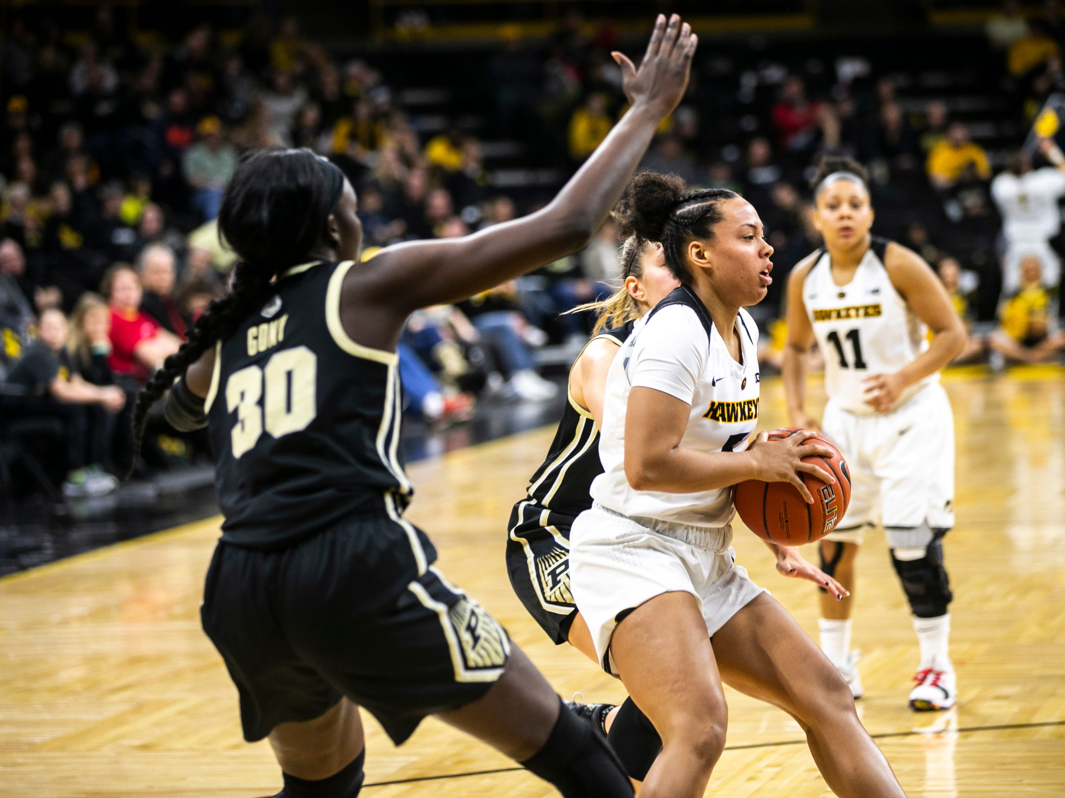 Iowa guard Alexis Sevillian (5) passes out to a teammate while being defended by Purdue forward Nyagoa Gony (30) during a NCAA Big Ten Conference women's basketball game on Sunday, Jan. 27, 2019, at Carver-Hawkeye Arena in Iowa City, Iowa.