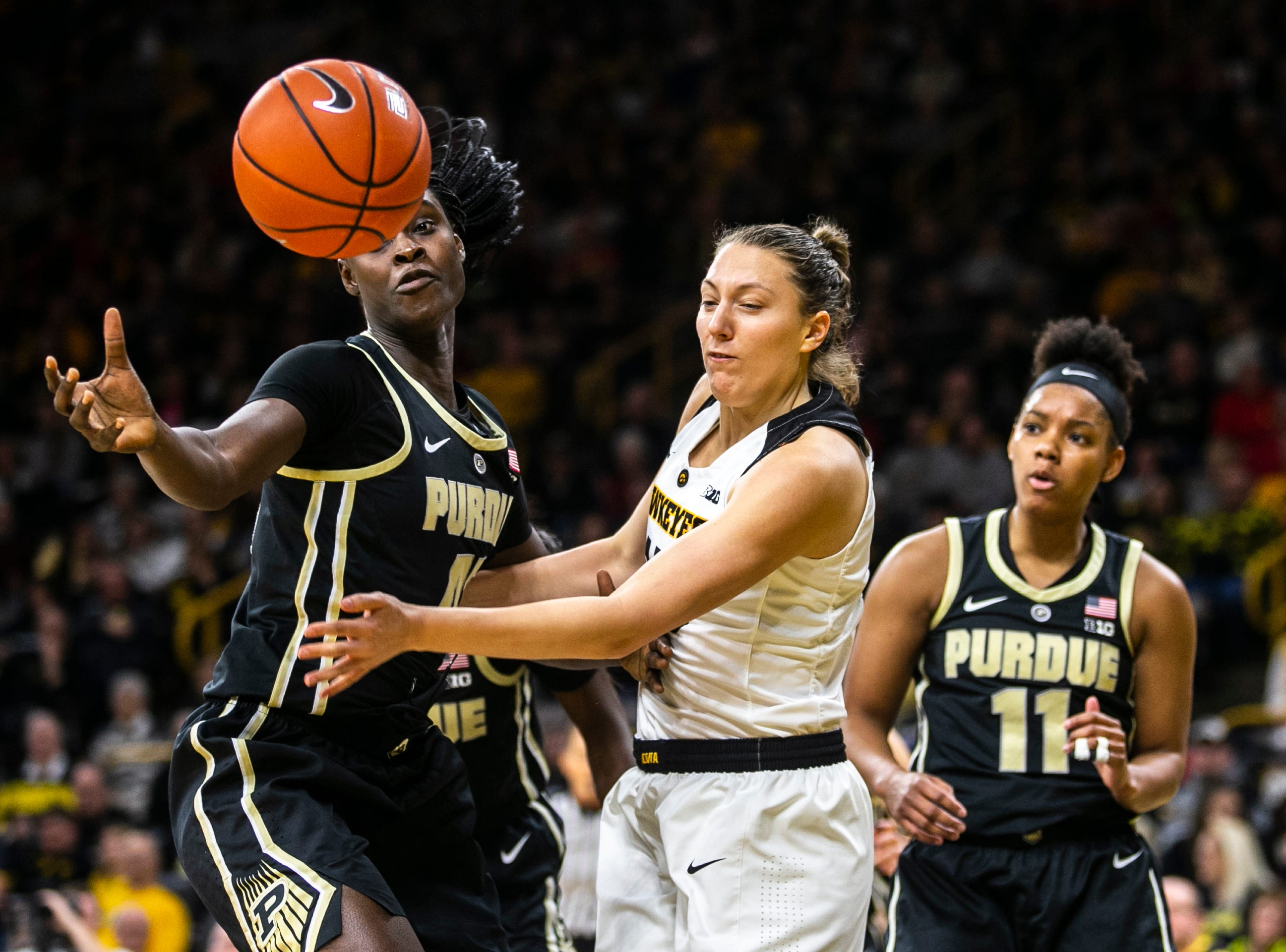 Iowa forward Amanda Ollinger, center, chases down a loose ball against Purdue center Fatou Diagne during a NCAA Big Ten Conference women's basketball game on Sunday, Jan. 27, 2019, at Carver-Hawkeye Arena in Iowa City, Iowa.