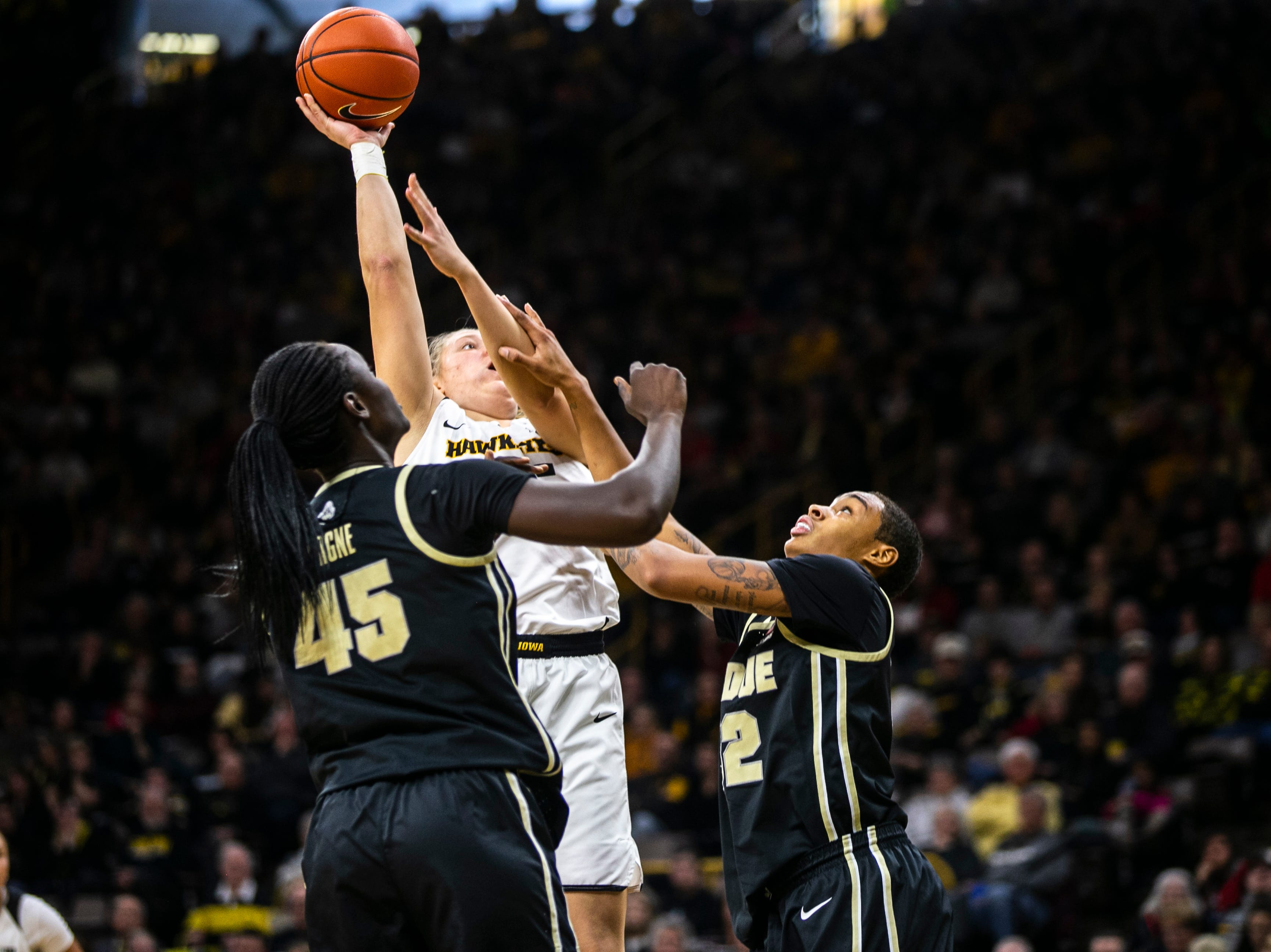 Iowa's Monika Czinano (25) gets defended by Purdue center Fatou Diagne (45) and forward Ae'Rianna Harris (32) during a NCAA Big Ten Conference women's basketball game on Sunday, Jan. 27, 2019, at Carver-Hawkeye Arena in Iowa City, Iowa.
