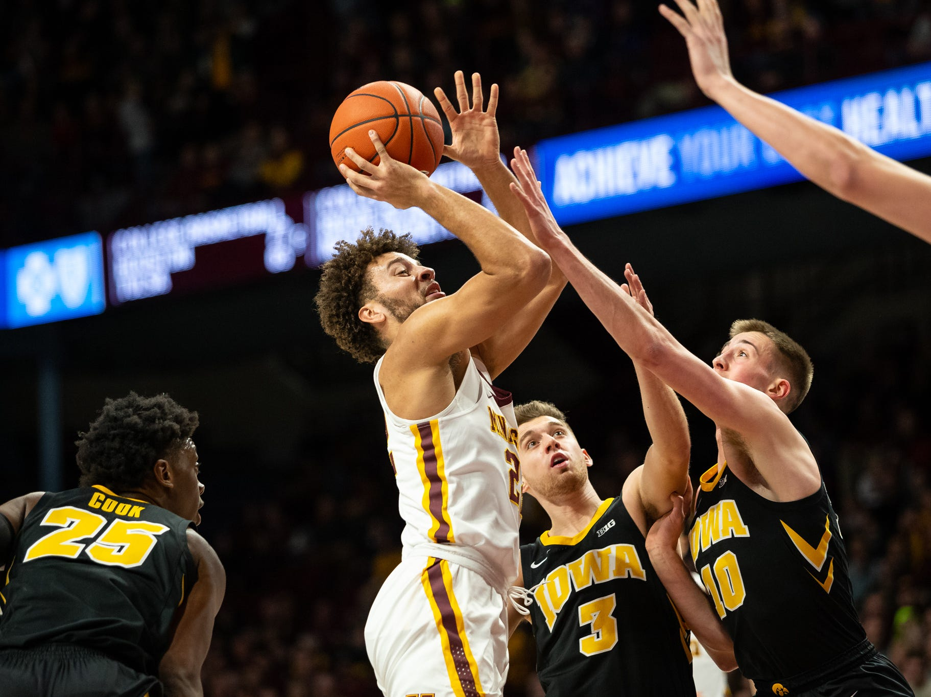 Jan 27, 2019; Minneapolis, MN, USA; Minnesota Gophers guard Gabe Kalscheur (22) shoots the ball over Iowa Hawkeyes guard Joe Wieskamp (10) and guard Jordan Bohannon (3) during the first half at Williams Arena. Mandatory Credit: Harrison Barden-USA TODAY Sports