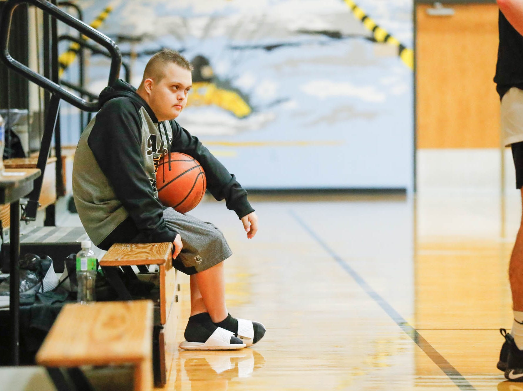 Jalen Pigg, the step son of Salem High School Boys Basketball Coach, Mike Brown, rests on the bleachers during a team practice at Salem High School in Salem Ind. on Tuesday, Jan. 23, 2019. Jalen, who was born with Down Syndrome, is now battling a form of leukemia but has a lot of support from the team. After a stint at Riley Children's Hospital during the holidays, Pigg is working to build his strength and endurance back up.