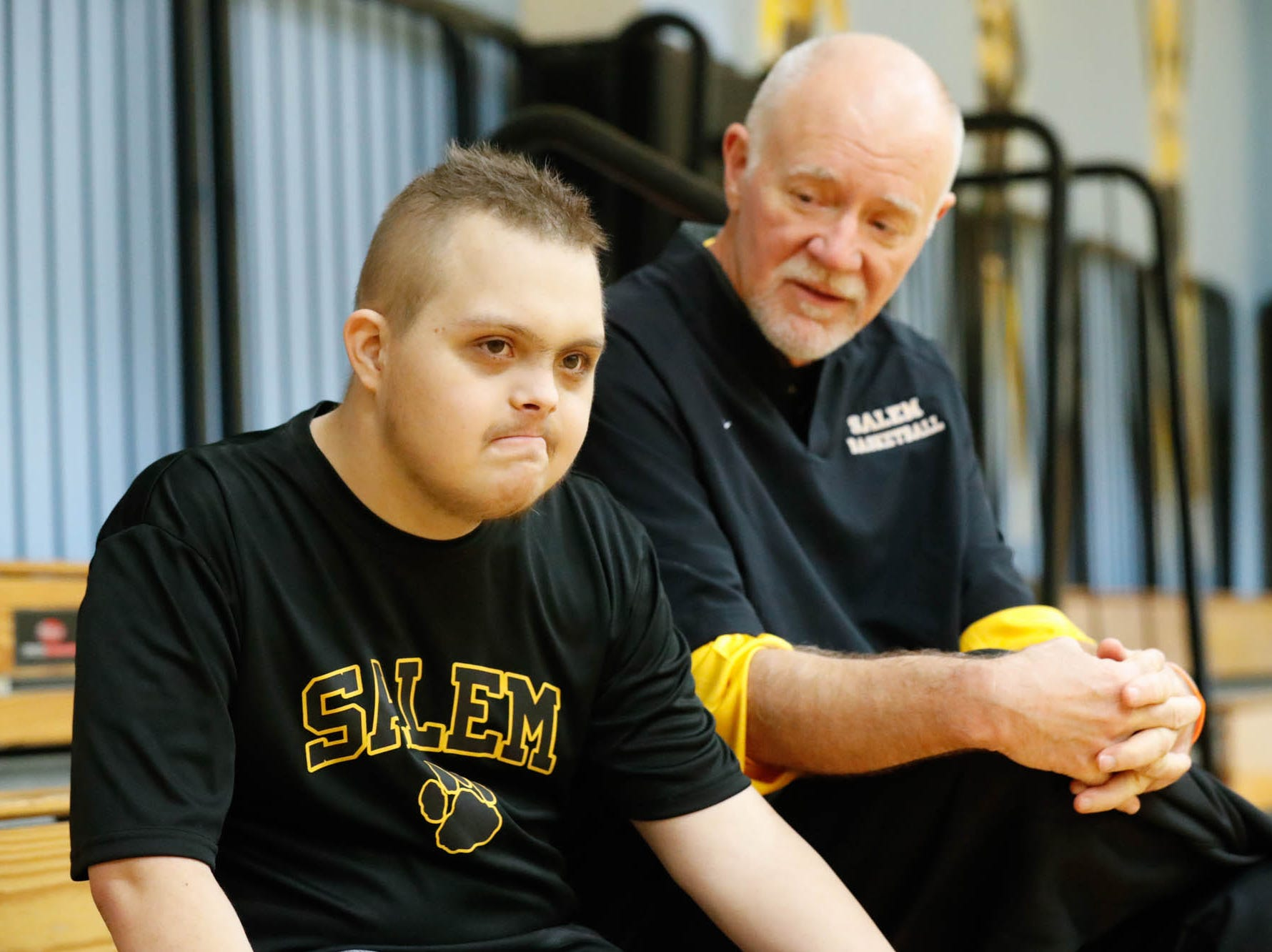 Jalen Pigg, left, and his step dad, Salem High School Boys Basketball Coach Mike Brown, right, rest for a moment on the bleachers during a team practice at Salem High School in Salem Ind. on Tuesday, Jan. 23, 2019. Jalen, who was born with Down Syndrome, is now battling a form of leukemia but has a lot of support from the team. After a stint at Riley Children's Hospital during the holidays, Pigg is working to build his strength and endurance back up to again help Brown with his coaching.