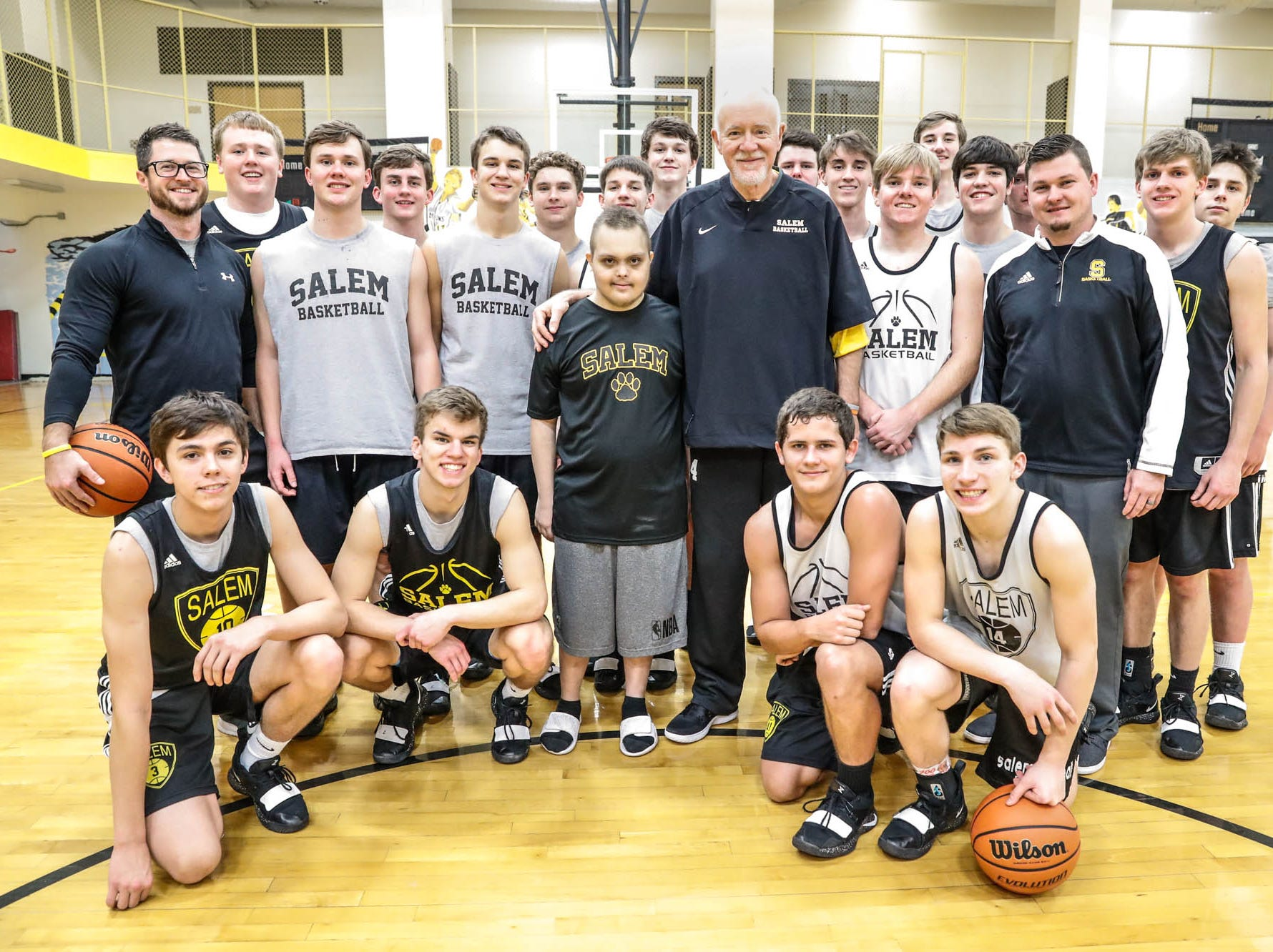 Jalen Pigg, center left, poses for a photo with step dad and Salem High School Boys Basketball Coach, Mike Brown, center right, with the boys basketball team at Salem High School in Salem Ind. on Tuesday, Jan. 23, 2019. Jalen, who was born with Down Syndrome, is now battling a form of leukemia but has a lot of support from the team and his family.