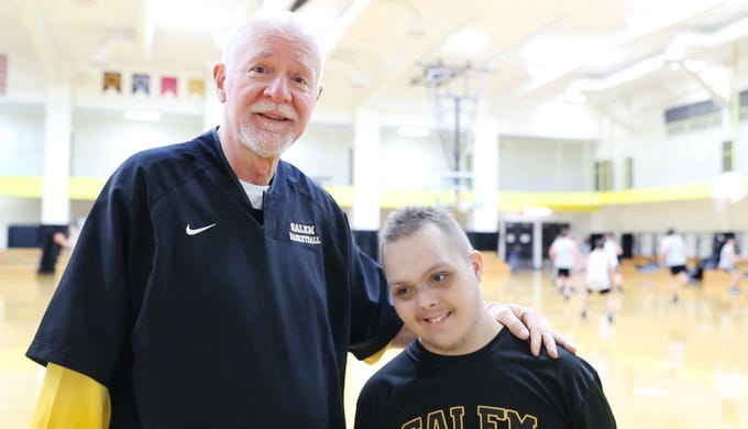 Jalen Pigg, left, and his step dad, Salem High School Boys Basketball Coach Mike Brown, right, are interviewed during a team practice at Salem High School in Salem Ind. on Tuesday, Jan. 23, 2019. Jalen, who was born with Down Syndrome, is now battling a form of leukemia but has a lot of support from the team. After a stint at Riley Children's Hospital during the holidays, Pigg is working to build his strength and endurance back up to again help Brown with his coaching.