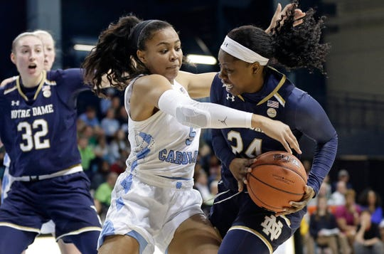 North Carolina's Stephanie Watts (5) reaches for the ball against Notre Dame's Arike Ogunbowale during the first half of an NCAA college basketball game in Chapel Hill, N.C., Sunday, Jan. 27, 2019. Notre Dame's Jessica Shepard (32) looks on.
