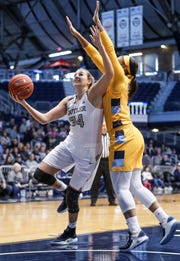 Marquette Golden Eagles forward Erika Davenport (12) tries to stop a shot by Butler Bulldogs forward Tori Schickel (34) in the first half of the game at Hinkle Fieldhouse in Indianapolis, Sunday, Jan. 27, 2019. Butler lost to Marquette, 58-87.