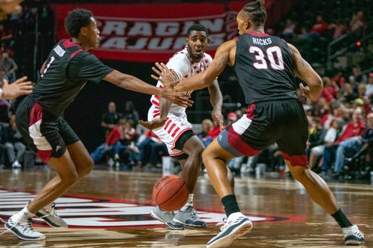 UL's P.J. Hardy passes the ball between two Troy defenders as the Ragin' Cajuns take on the Trojans at the Cajundome on Jan. 26, 2019.