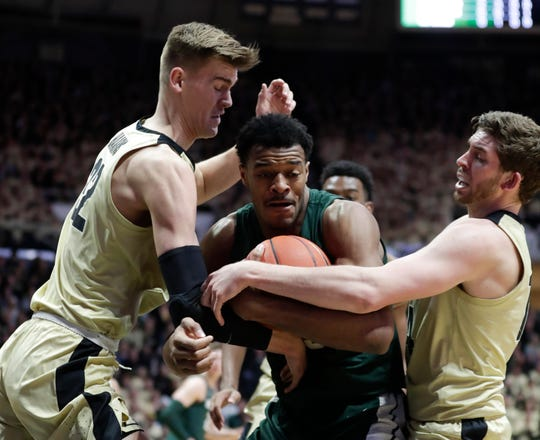Michigan State forward Xavier Tillman (23) is tied up by Purdue center Matt Haarms (32) and guard Ryan Cline (14) during the first half of an NCAA college basketball game in West Lafayette, Ind., Sunday, Jan. 27, 2019.