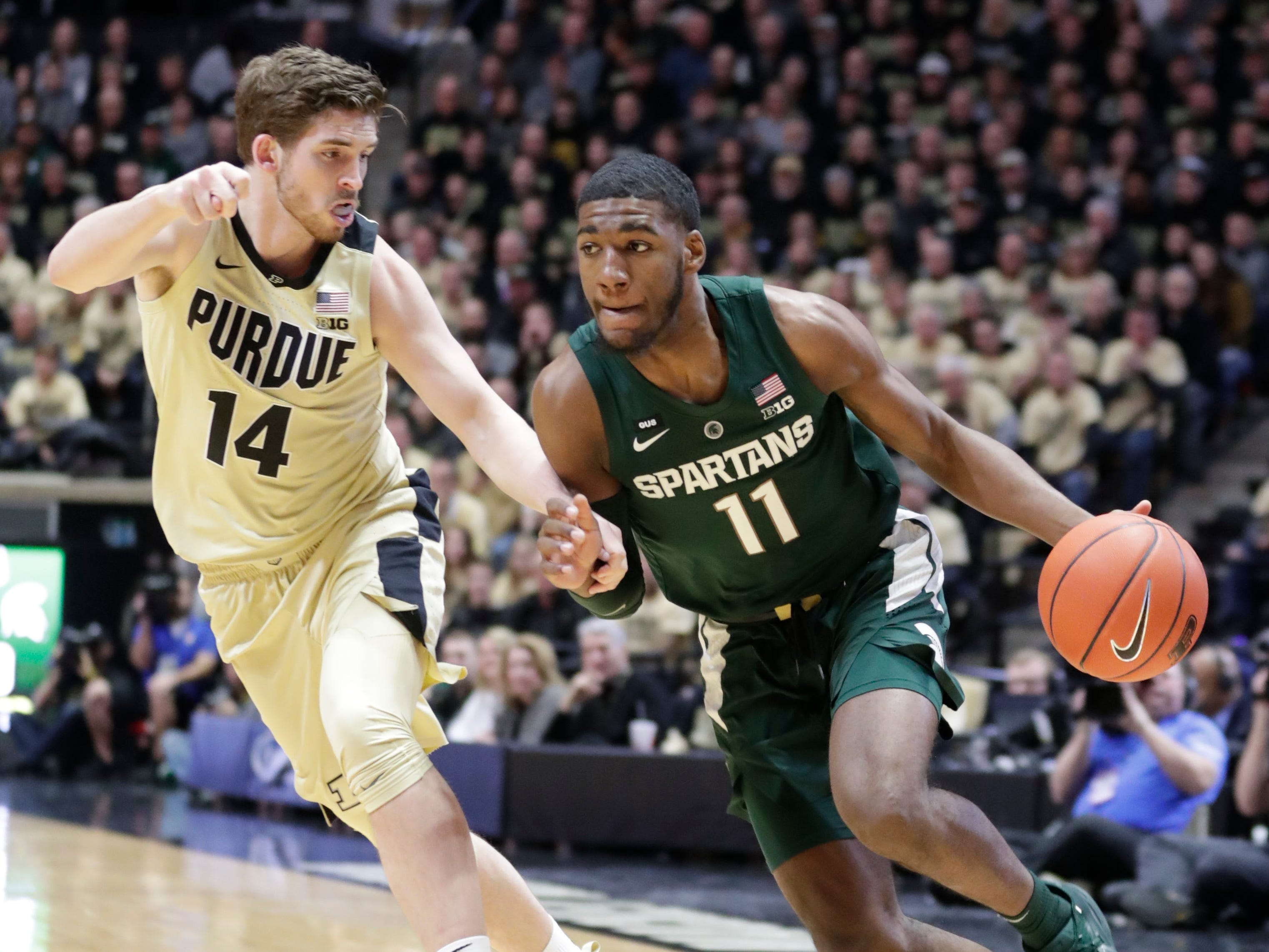 Michigan State forward Aaron Henry (11) drives on Purdue guard Ryan Cline (14) during the first half of an NCAA college basketball game in West Lafayette, Ind., Sunday, Jan. 27, 2019.