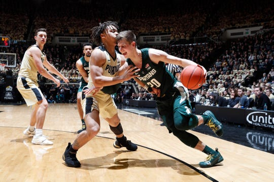 Michigan State Spartans guard Matt McQuaid (20) dribbles the ball as Purdue Boilermakers guard Carsen Edwards (3) defends during the first half at Mackey Arena.