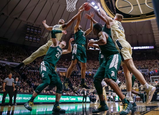 Nojel Eastern #20 and Matt Haarms #32 of the Purdue Boilermakers reach for a rebound against Kenny Goins #25 of the Michigan State Spartans at Mackey Arena on January 27, 2019 in West Lafayette, Indiana.