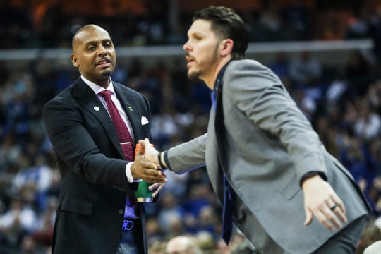 Memphis coach Penny Hardaway, left, and assistant coach Mike Miller slap hands during Sunday afternoon's game against UCF.
