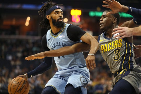 Memphis Grizzlies guard Mike Conley looks to pass the ball against the defense of Indiana Pacers guard Aaron Holiday during their game at the FedExForum on Saturday, Jan. 26, 2019.