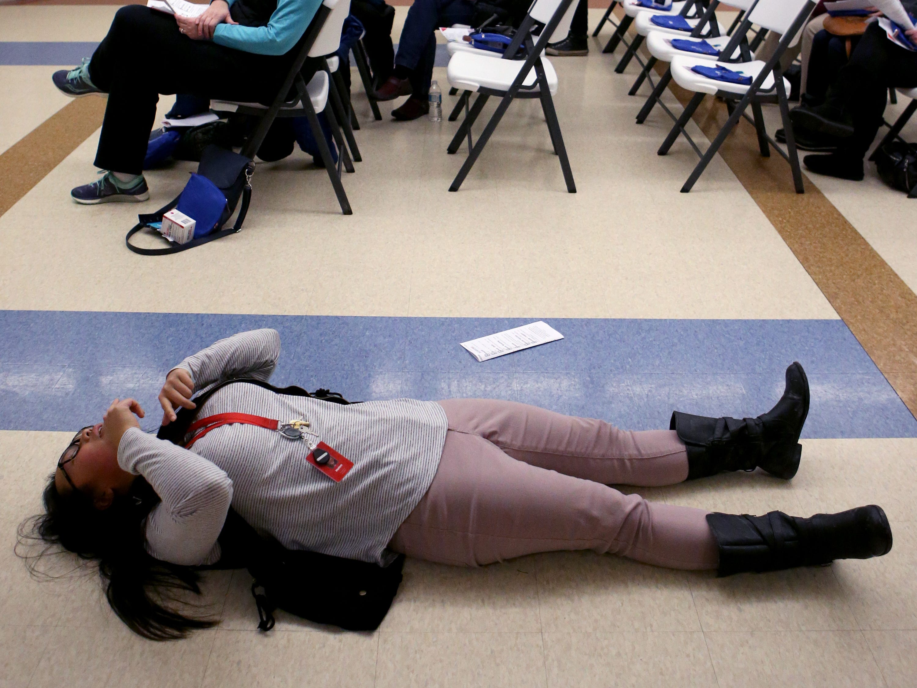 Helen Lai, a prevention specialist from the Aids Resource Center of Wisconsin, demonstrates making a victim flat and head tilted to administer nasal Narcan to counteract an opiate overdose during workshop at the Salvation Army's Greenfield facility on Jan. 24.