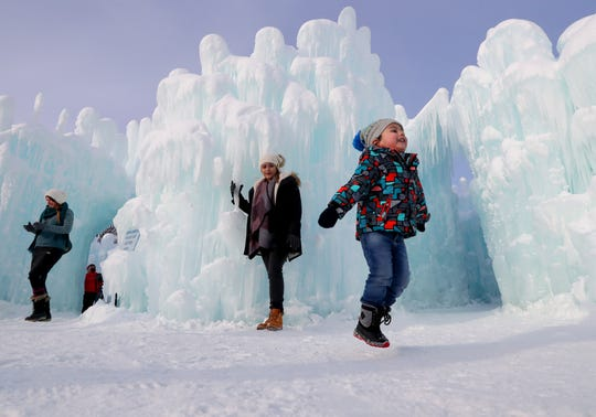 Alan Aquino, 3, hops near the ice formations as his mother, Anna Aquino, both of Chicago, waits to have her photo taken by her husband, Alberto (not pictured).